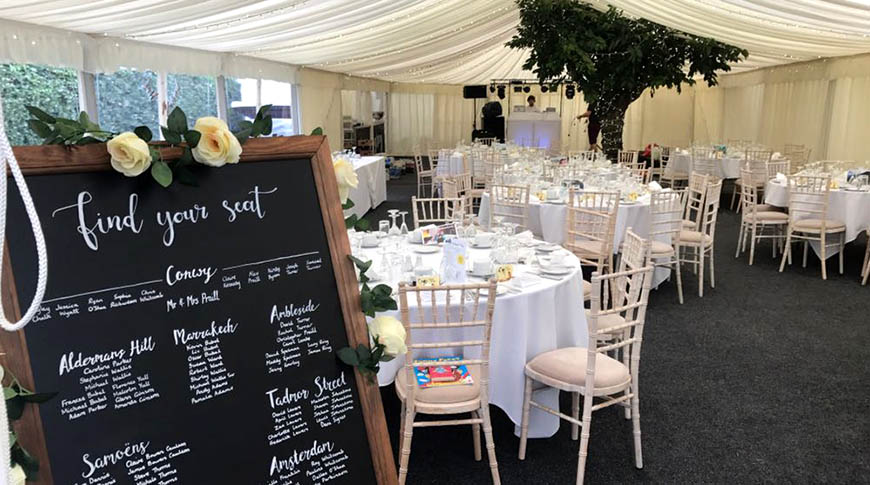 internal marquee shot showing tables and chairs in ivory and cream.
